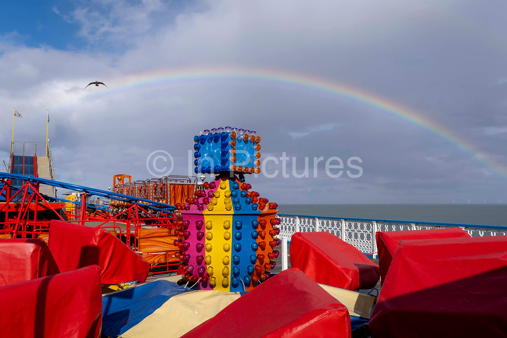 A rainbow showing the spectrum of colours is seen arcing across the sky above Llandudno pier where a fairground ride is covered, on 4th October 2021, in Llandudno, Gwynedd, Wales.