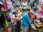 11 OCTOBER 2015 - BANGKOK, THAILAND: Shoppers look for toys in the Saphan Lek market on what the Bangkok city government is saying was the last day of business for the market. Many shops in the market are already closed. Street vendors and illegal market vendors in the Saphan Lek area will be removed in the next two weeks as a part of an urban renewal project coordinated by the Bangkok Metropolitan Administration. About 500 vendors along Damrongsathit Bridge, popularly known as Saphan Lek, have until Monday, October 11,  to relocate. Vendors who don't move will be evicted. Saphan Lek is one of several markets and street vending areas being closed in Bangkok this year. The market is known for toy and replica guns, bootleg and pirated DVDs and CDs and electronic toys.    PHOTO BY JACK KURTZ