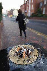Ash tray on top of litter bin with dogends