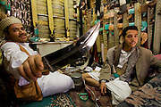 A traditional dagger seller brandishes one of the jambiyas (daggers) in his broad inventory at his market stall in the souk of Sanaa, Yemen.