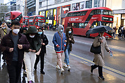 As Londoners await the imminent second coronavirus lockdown it's business as usual in the West End with large numbers of people, some wearing face masks and some not, brave the rain on Oxford Street to go shopping on what will be the last weekend before a month-long total lockdown in the UK on 1st November 2020 in London, United Kingdom. The three tier system in the UK has not worked sufficiently, to suppress the virus, and there have have been calls by politicians for a 'circuit breaker' complete lockdown to be announced to help the growing spread of the Covid-19.