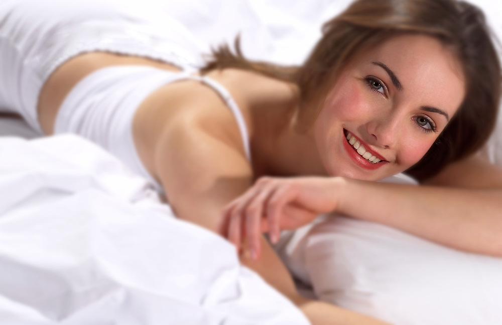 Smiling woman wearing white tank top relaxing in bed and looking at the camera