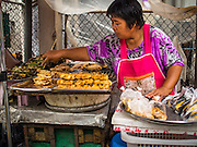 30 AUGUST 2014 - BANGKOK, THAILAND:  A vendor grills bananas at a street stall in the Thonburi section of Bangkok.     PHOTO BY JACK KURTZ