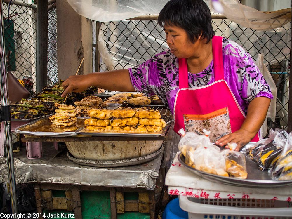30 AUGUST 2014 - BANGKOK, THAILAND:  A vendor grills bananas at a street stall in the Thonburi section of Bangkok.     PHOTO BY JACK KURTZ