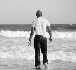 Young man in wet clothes walking into the ocean