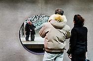 Nederland,  Rotterdam, 2 febr 2014<br /> Twee stellen die elkaar kennen staan op twee perrons in metrostation en hebben kontakt met elkaar via een rond gat tussen de sporen.<br /> Foto: Michiel Wijnbergh