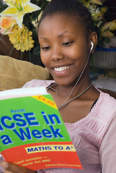 Girl sitting on sofa listening to walkman and studying for school exams,