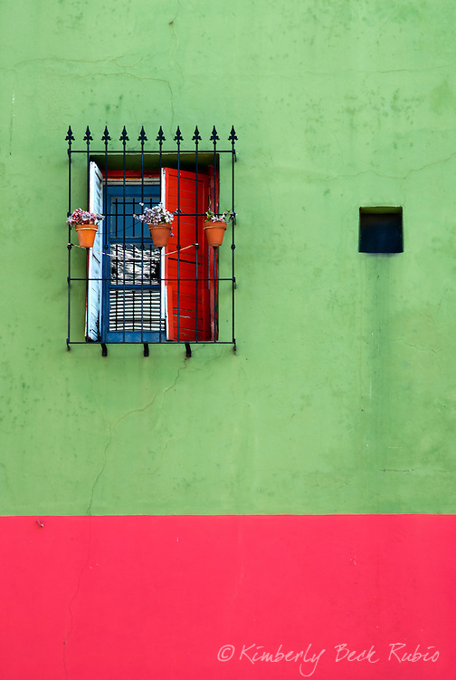 Brightly colored wall with a reflective. barred window in La Boca, Buenos Aires, Argentina.