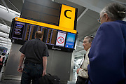Passengers read flight departure information in the departures concourse at Heathrow's Terminal 5.