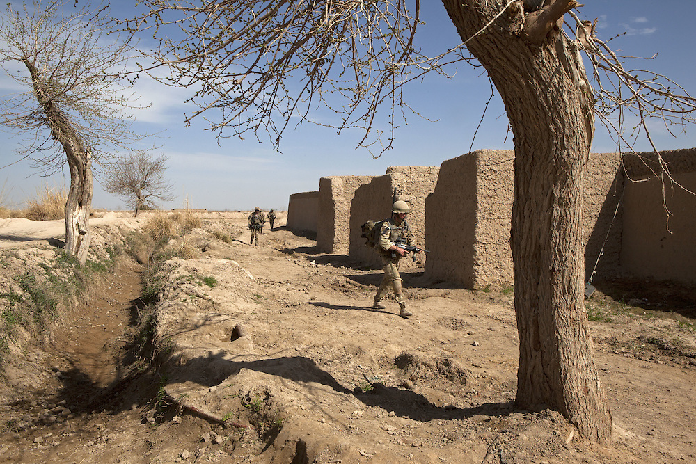 British soldiers of 16 Air Assault Bde's elite BRF (Brigade Reconnaissance Force) move from compound to compound crossing open fields and using dried up irrigation ditches for cover as they search for weapons and explosives as part of an operation in the village of Kakaran in Helmand Province, Southern Afghanistan on the 14th of March 2011.