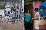 Two women talk outside their house. Cidade de Deus / City of God favela in Rio de Janeiro, made infamous by the film of the same name, is a bustling community of close to 100,000 inhabitants, with numerous cultural and social projects.