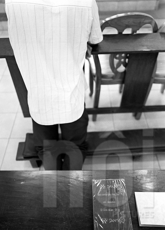 A man praises kneeled on a bench in a church of Vientiane, Laos, Asia