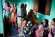 Jesmin Akhter, 26 (3rd from right, in turquoise & blue), sells her products in one of her 'marketplaces', Jerai Villlage, Gobindagonj Upazila, Gaibandha, Bangladesh on 19th September 2011. She has found financial independence and contributes to her household income by working as a saleswoman, earning 3500 - 5000 Bangladeshi Taka per month. She is the top saleswoman under her 'hub', out of 30 women. Having worked for about 2.5 years, she cycles from village to village and door to door in a country where women on bicycles is an extremely uncommon sight. She is one of many rural Bangladeshi women trained by NGO CARE Bangladesh as part of their project on empowering women in this traditionally patriarchal society. Named 'Aparajitas', which means 'women who never accept defeat', these women are trained to sell products in their villages and others around them from door-to-door, bringing global products from brands such as BATA, Unilever and GDFL to the most remote of villages, and bringing social and financial empowerment to themselves.  Photo by Suzanne Lee for The Guardian