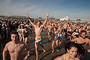 Swimmers running toward the water at the annual Pier Swim on New Year's Day, Narragansett, Rhode Island.