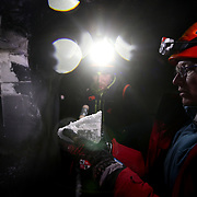 Glaciologist Andrea Fischer and Environmental Physicist Pascal Bohleber, from the Austrian Institute for Interdisciplinary Mountain Research,  look at a sample of ice after extraction inside an artificial ice tunnel of Schaufelferner glacier at Stubaier glacier ski resort near Neustift im Stubaital, Austria, October 22, 2018. REUTERS/Lisi Niesner