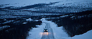 Car travels through arctic wilderness at nightfall by Kilpisjarvi on route from Norway into Finland