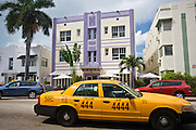 Yellow taxi cab passing Hotel Shelley on Collins Avenue, at South Beach, Miami, Florida, USA