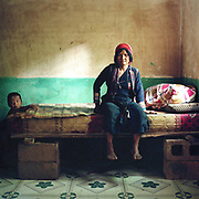 An Aini ethnic minority woman sits on a bed with a young boy in her home in Xiang Dao Ya village. Costume styles in the past were identified by discrete regions and sub regions, but due to a number of factors some groups are more widely dispersed.  This may be due to migration or search for land, and more recently, as a result of re-settlement of groups by the Chinese government, made necessary by the construction of new roads, reservoirs and hydroelectric schemes. The People's Republic of China recognises 55 ethnic minority groups in China in addition to the Han majority. The ethnic minorities form 9.44% of mainland China and Taiwan's total population and the greatest number can be found in Yunnan Province, 34% (25 ethnic groups).