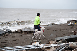 © London News Pictures. 05/01/2014. Aberystwyth, UK.  A man running with his dog though damage caused to Aberystwyth promenade which is littered with debris following days of high tides and storms. Much of the seafront has been severely damaged by the pounding pif the waves, with the likely cost of repairs running into the millions of pounds. Photo credit Keith Morris: LNP