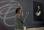 A tourist takes a selfie near a Goya portrait, sponsored by Credit Suisse and advertised on a construction hoarding outside the National Portrait Gallery.