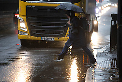 © Licensed to London News Pictures. 14/09/2021. London, UK. A woman attempts to jump over a puddle during heavy rain in Greenwich, South East London  . A yellow weather warning for rain is in place in parts of England . Photo credit: George Cracknell Wright/LNP