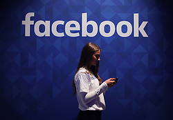 File photo dated 03/11/15 of a woman using her phone under a Facebook logo. The head of the foundation created by philanthropist George Soros has called for an independent review into Facebook's lobbying practices amid allegations the site used a PR firm to undermine its critics.