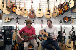 First Minister Nicola Sturgeon (left) is shown how to play a guitar by the SNP's local candidate Mhairi Black while on the general election campaign trail in Paisley.