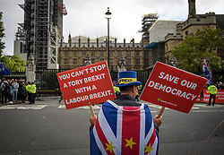 © Licensed to London News Pictures. 25/09/2019. London, UK. An anti Brexit protestor stands outside the Houses of Parliament in Westminster on the day that MPs return. The Supreme Court in London yesterday ruled that Parliament had been suspended illegally after British Prime Minster Boris Johnson prorogued parliament just weeks before the UK is due to leave the EU on October 31st. Photo credit: Ben Cawthra/LNP