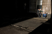 Resting workmen and businessman in a shaft of early spring light in a side street in the capital's financial district. This is Lombard Street, originally a piece of land granted by King Edward I to goldsmiths from the part of northern Italy known as Lombardy (larger than the modern region of Lombardy). It is a narrow and usually dark sidestreet near the Bank of England in the heart of what is called the Square Mile - the inner-part and oldest quarter of London occupied first by the Romans 2,000 years ago. Nowadays the City of London is home to banks and financial institutions but also with a resident population of under 10,000 but a daily working population of 311,000.