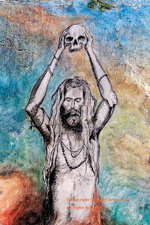 Death and the Sadhu: This colourful wall painting depicts a Hindu Sadhu (Holy man) using both hands to hold a humans skull overhead, Varanasi India.