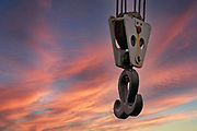 Crane hook hanging on steel cables with a sunset sky background