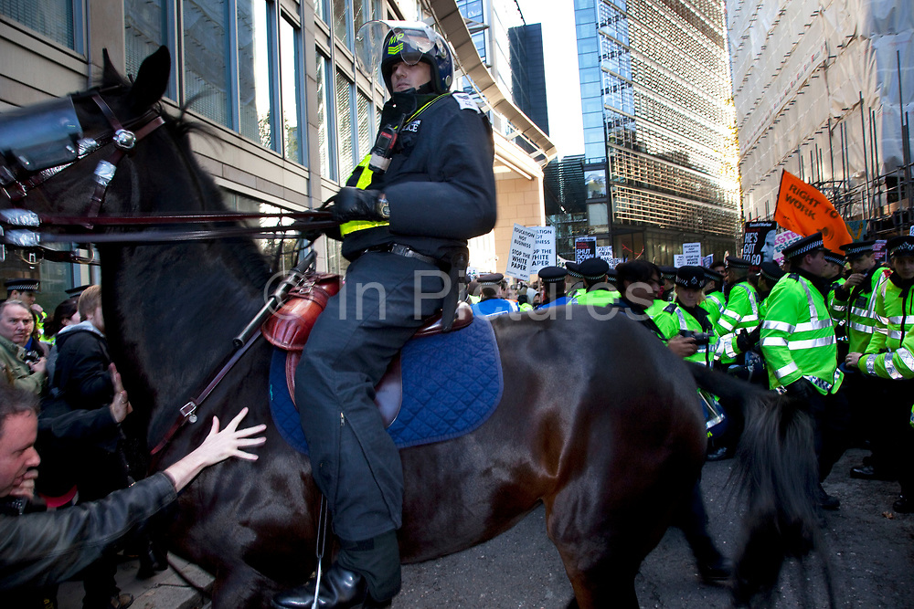 """Police horses in riot gear are deployed as scuffles break out in The City of London along New Fetter Lane as students march through central London to protest against rises in tuition fees and changes to higher education. The police were out in force as thousands of students marched through central London. Some 4,000 officers were on duty, as demonstrators marched peacefully in a protest against higher tuition fees and """"privatisation"""" in universities. The police estimated that about 2,000 people took part in the demonstration."""
