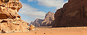 A young man looks out from his high perch over the desert in Wadi Rum, Jordan.