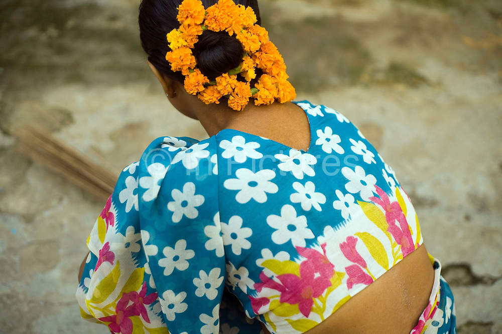 A South Indian maid sweeps a courtyard with flowers in her hair, Janakpuri, New Delhi, India