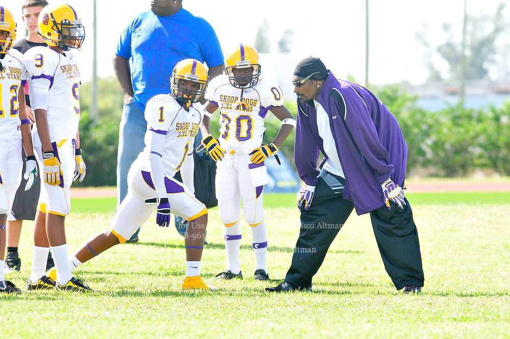 Snoop Dogg lines up to play defense against his Vikings offense during their ewarm up sessiion before Snop Bowl V111Snoop Dogg sits and watches his Vikings team warm up before the 8th Annual Snoopp Bowl. Bowl V111 in Miami SaT FEB 6,2010.  SNOOP DOG GET HIS GROOVE ON WHILE HIS TEAM WARMS UP FOR THE SNOOP BOWL,,,,,ITS THE  8th year in a row that Snoop has brought his Snoop Dogg's  AllStar Team from California to the Super Bowl to play an exihibiiton game.Muscian and performer Snoop Dogg hosts the 8th annual Snoop Bowl at  Traz Powell Stadium in Miami Saturday Feb 6,2010. Snoop coaches the Vikings teams at the Snoop Bowl and it it the All Star team from Pomona California of the Steelers that he coaches all year.Dion Sanders was coaching the first game at the Snoop Bowl,wearing red coaching red team.Photo©Suzi Altman/SuziSnaps