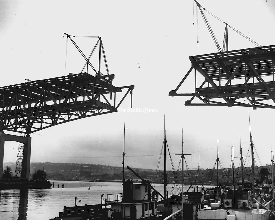 With the north end, at right, seemingly suspended in the air, the freeway bridge over Lake Union was reported three weeks ahead of schedule. Workmen planned to set into place the first nine, 70-foot-long steel beams to connect the two sections. (Johnny Closs / The Seattle Times, 1980)