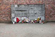 Wall of Death with flower offerings, Auschwitz, Poland.