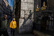 Passers-by and sunlit railings of St. Mary Woolnoth church on Lombard Street, on 10th May 2017, in the City of London, England.