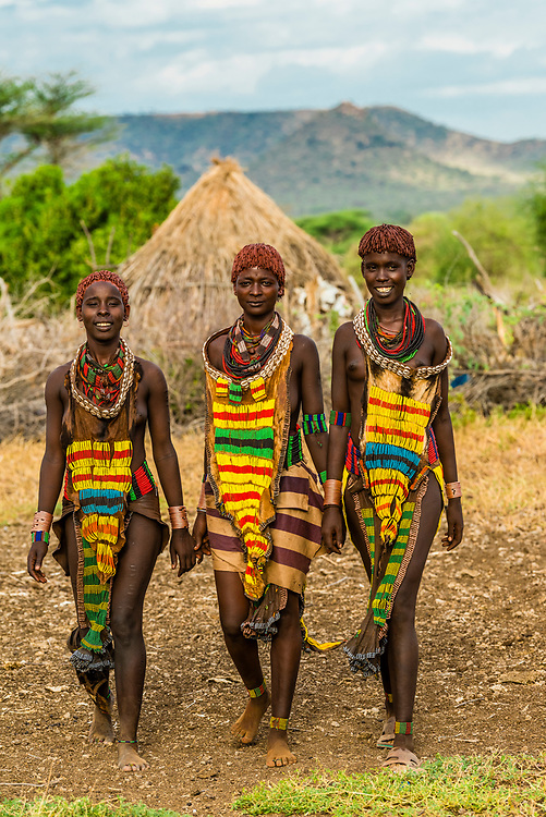 Hamer tribe women holding hands and walking in their village, Omo Valley, Ethiopia.