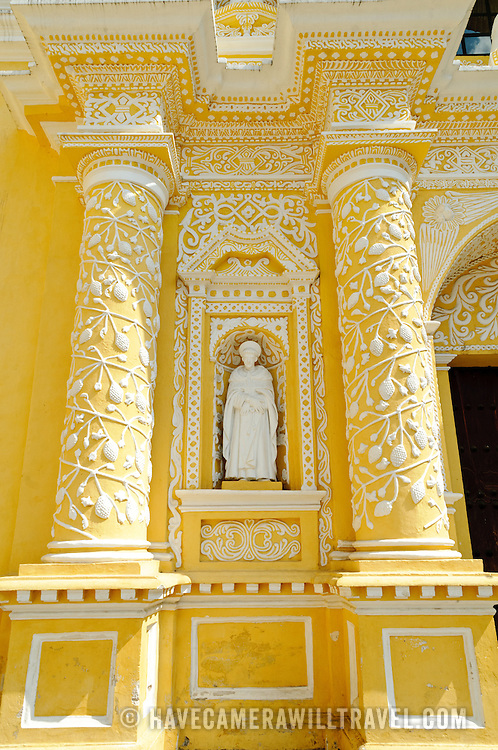 Statue on the front of the distinctive  and ornate yellow and white exterior of the Iglesia y Convento de Nuestra Senora de la Merced in downtown Antigua, Guatemala.