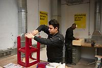 DEU, Deutschland, Germany, Berlin, 17.12.2015: Flüchtlinge arbeiten in einer Werkstatt der Flüchtlings-Initiative der Handwerkskammer, arrivo Berlin, in der Innung für Metall- und Kunststofftechnik. Mohamad Al Homsi aus Syrien lackiert einen Tisch.