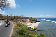 Nusa Penida, Indonesia - September 29, 2017: Two tourists tour the Indonesian island of Nusa Penida on a rented motor scooter, driving past a part of the island dotted with seaweed farms. Scooters are a popular means of transport around the island, located off the coast of Bali.