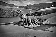 Passengers push an airplane into the wind to cool down an engine before takeoff. Mestia. 2004.