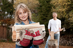 Smiling girl carrying firewood with father in background