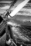 Sailor tending the jib of heeled over sailboat in the Bay, San Francisco