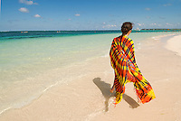 A teenage girl wrapped in a colorful sarong enjoys the white sand, turquoise water and blue sky of Bavaro Beach, a popular tourist destination.