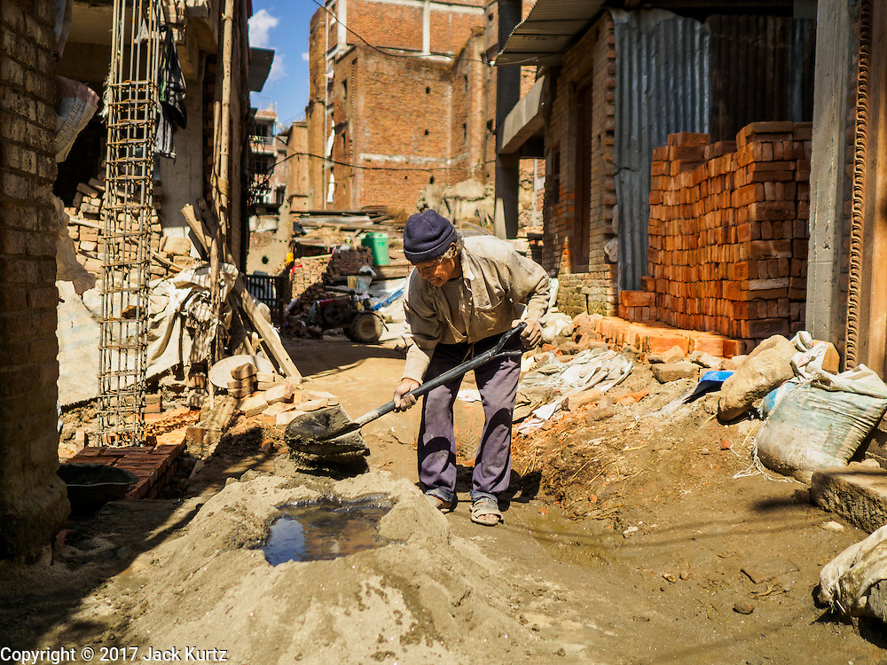 03 MARCH 2017 - BHAKTAPUR, NEPAL: A man mixes mortar to use in rebuilding a home in Bhaktapur. Bhaktapur, a popular tourist destination and one of the most historic cities in Nepal was one of the hardest hit cities in the earthquake. Recovery seems to have barely begun nearly two years after the earthquake of 25 April 2015 that devastated Nepal. In some villages in the Kathmandu valley workers are working by hand to remove ruble and dig out destroyed buildings. About 9,000 people were killed and another 22,000 injured by the earthquake. The epicenter of the earthquake was east of the Gorka district.      PHOTO BY JACK KURTZ