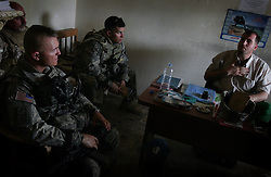 Lt Col. John Norris (left) commanding officer of the 4BN 23rd Infantry Regiment of the 172nd Stryker Brigade and the commanding officer of the battalion's Bravo Company - Capt. Brad Velotta - discuss the discovery of weapons and supplies stored in the offices of the Iraqi Islamic Party in the Baghdad Sunni neighborhood of Ghazaliyah wth the local director, Hassan Saman. The discovery - part of an operation by bolstered US and Iraqi forces in the hopes of getting a handle on the extraordinary numbers of sectarian killings in Baghdad - was carried out in Baghdad, Iraq on Tuesday August 15, 2006. The brigade, which was in the process of rotating home at the end of a year tour in Mosul and northwestern Iraq, was diverted to the capital for an undetermined number of additional months.