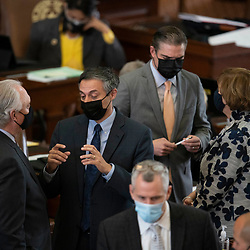 Austin, TX USA March 31, 2021:  State Rep. Giovanni Capriglione, R-Southlake, (l) with Rep. Morgan Meyer, (r)  with others on the floor of the Texas House of Representatives during routine bill readings at the 87th Texas legislative session. Emergency bills include power company regulation, border security and the coronavirus response.