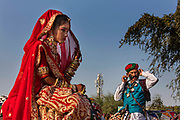 A young girl wearing a traditional bridal outfit with a man in traditional dress flaunting his moustache in front of a telecoms tower at the Desert Festival on 29th January  in Jaisalmer, Rajasthan, India. It is an annual event that take place in February month in the beautiful city Jaisalmer. The bridal dowry is a rich aray of silver and gold jewelry and the hands and arms are adorned with henna patterns. The number of smartphone users in India has  reached over 700 million in 2021 with over 1 billion mobile connections.